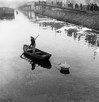 0153229 © Granger - Historical Picture ArchiveMARINIER.   french bargeman in Deule canal near Lille , north of France, towing candle to find the body of young Nelly Verbrugghe february 13, 1959 (according to an old custom, the candle extinguishes when it passes over a drowned body). Full credit: AGIP - Rue des Archives / Granger, NYC -- All rig