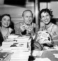 0153593 © Granger - Historical Picture ArchiveMAURICE DEKOBRA.   French writer and scriptwriter Maurice Dekobra showing the price of a book with his hands at Veteran Writers Fair in Paris june 1, 1956 on his side cabaret dancer Fortuna. Full credit: AGIP - Rue des Archives / Granger, NYC -- All Rights Reserved.