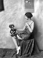 0175640 © Granger - Historical Picture ArchiveZIEGFELD FOLLIES, c1920.   A Ziegfeld Follies dancer and model posing with a doll. Photograph, c1920.
