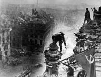 0073390 © Granger - Historical Picture ArchiveWWII: BERLIN FALLEN, 1945.   Two Russian soldiers hoisting the Soviet flag on the destroyed Reichstag building. Picture taken May 1945 by Yevgeny Khaldei.