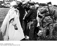 0077554 © Granger - Historical Picture ArchiveALGERIAN WAR, 1956.   French police officer and soldier search civilians on the Algiers-Tablat highway, the scene of repeated attacks on passing vehicles by FLN groups, April 1956.