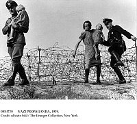 0084730 © Granger - Historical Picture ArchiveNAZI PROPAGANDA, 1939.   'Flight from the Polish Terror. A mother and her child work themselves across barbed wire.' Nazi propaganda photograph, August 1939, promoting the fictitious Polish 'terror' before Germany's invasion of Poland in September 1939.