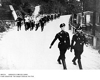 0085254 © Granger - Historical Picture ArchiveGERMANY: FORCED LABOR.   SS officers leading a march of forced laborers from a concentration camp near Hohnstein in eastern Germany. Photographed 1933-34.