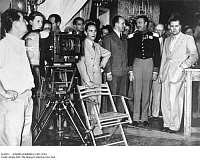0120431 © Granger - Historical Picture ArchiveJOSEPH GOEBBELS (1897-1945).   German Nazi Party leader. Goebbels (center) at the shooting of the film 'Preussische Liebesgeschichte (Prussian Love Story),' 1938. At left is Italian film critic Vittorio Mussolini, son of Benito Mussolini. To the left of Goebbels is Dr. Lehnich, Willy Fritsch in the costume of Prinz Wilhem, and Secretary of State Karl Hanke.