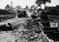 0126466 © Granger - Historical Picture ArchiveWORLD WAR II: LATVIA, 1944.   A truck carrying German troops driving through the destroyed village of Madona, Latvia. At right is a wrecked T-34 Panzer tank. Photograph, August 1944.