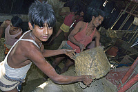 0133688 © Granger - Historical Picture ArchiveBANGLADESH: CHILD LABOR.   A boy working alongside men in a cement factory in Dhaka, Bangladesh. Photograph, 27 February 2007. Full credit: Lillehaug - ullstein bild / Granger, NYC -- All Rights Reserved.