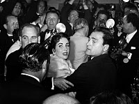 0217076 © Granger - Historical Picture ArchiveELIZABETH TAYLOR (1932-2011).   American (English-born) actress. Surrounded by photographers at the Cannes Film Festival with her husband, theater and film producer Mike Todd (right foreground), May 1957.