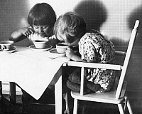 0218506 © Granger - Historical Picture ArchiveDAILY LIFE.   Germany, children at the table, two girls drinking and spooning probably hot chocolate, date unknown, around 1933, photo by R. Schuler.