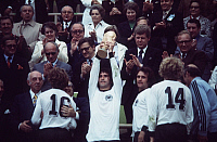 0220590 © Granger - Historical Picture ArchiveSOCCER.   1974 FIFA World Cup in Germany Final in Munich: Germany 2 - 1 Netherlands - Gerd Mueller holding up the trophy at the award ceremony towards the right: Wolfgang Overath, Hoeness, coach Helmut Schoen - - 07.07.1974 Identical with image no xy.