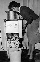 0224485 © Granger - Historical Picture ArchiveTECHNOLOGY.   Germany, Bavaria, Munich - Woman demonstrates the Glastra potato husker for industrial purposes by Brilliant Industries at the Hotel and Restaurant Fair - 13.09.1957.