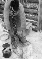 0231706 © Granger - Historical Picture ArchivePEOPLE.   Trapper living in Canada: Man is cutting up frozen meat with an axe - Photographer: Felix H. Man - Published by: 'Koralle' 06/1934 Vintage property of ullstein bild.