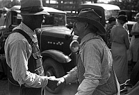 0119379 © Granger - Historical Picture ArchiveKANSAS: FARMERS, 1938.   Two farmers shake hands at a farm auction in Oskaloosa, Kansas. Photograph by John Vachon in October 1938.