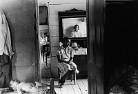 0122695 © Granger - Historical Picture ArchiveGEORGIA: FARM GIRL, 1940.   Daughter of a African American tenant farmer seated inside their farmhouse in Greensboro, Greene County, Georgia. Photograph by Jack Delano, June 1941.