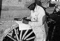 0118991 © Granger - Historical Picture ArchiveCOTTON PICKER, 1935.   An African American cotton worker calculates the weight of cotton in a notebook, Little Rock, Arkansas. Photograph by Ben Shahn in October 1935.