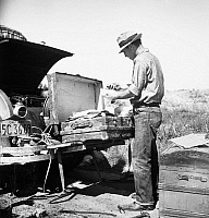 0092886 © Granger - Historical Picture ArchiveMIGRANT WORKER, 1938.   Migrant worker sorting luggage in San Joaquin Valley, California. Photograph, by Dorothea Lange, 1938