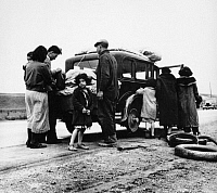 0131254 © Granger - Historical Picture ArchiveMEXICAN MIGRANTS, 1936.   A Mexican family of migrant workers with a flat tire along a road in California. Photograph by Dorothea Lange, February 1936.