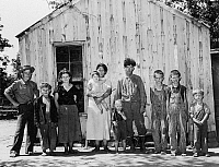 0131259 © Granger - Historical Picture ArchiveMIGRANT FAMILY, 1939.   A family of migrant workers standing in front of their two room shack in McIntosh County, Oklahoma. Photograph by Russell Lee, June 1939.
