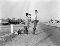 0268436 © Granger - Historical Picture ArchiveMIGRANT FAMILY, 1936.   A migrant family from Oklahoma standing along the highway between Blythe and Indio in California, after their car had broken down. Photograph by Dorothea Lange, 1936.
