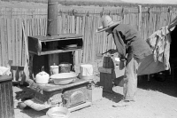 0352596 © Granger - Historical Picture ArchiveNEW MEXICO: HOMESTEADER.   Mrs. Faro Caudill pouring water over milk bucket to keep the milk cold outside of her temporary home in Pie Town, New Mexico. Photograph by Russell Lee, 1940.