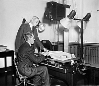 0123208 © Granger - Historical Picture ArchiveCENSUS RECORDING, 1937.   A member of the Social Security board photographing Census data under the supervision of Census Bureau Director William L. Austin. Photograph, 1937.