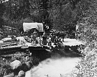 0216873 © Granger - Historical Picture ArchiveCOLORADO: EMIGRANTS, c1870.   Emigrant famillies posing in front of a covered wagon on a timber bridge over the rapids of the Upper Arkansas River, near Pueblo, Colorado. Photographed by William Gunnison Chamberlain, c1870.