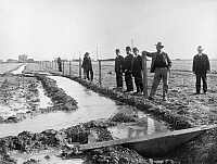 0125069 © Granger - Historical Picture ArchiveWYOMING: IRRIGATION, c1915.   A group of men standing behind a barbed wire fence on a field in northern Wyoming that is being irrigated with waters from the Shoshone River as part of the Shoshone Reclamation Project. Photographed c1915.