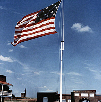 0259389 © Granger - Historical Picture ArchiveTHE STAR SPANGLED BANNER.   A replica of the 15 star American flag from 1814 at Fort McHenry in Baltimore Harbor, Maryland. Photograph, mid or late 20th century.