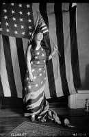 0621879 © Granger - Historical Picture ArchiveAMERICAN FLAG COSTUME, 1917.   Opera singer Fely Clement wearing a liberty cap and draped in the American flag. Photograph, 1917.