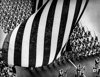 0621889 © Granger - Historical Picture ArchiveWWII: PARADE, c1942.   Soldiers marching with rifles and bayonets, with a flag flying above, during a parade during World War II. Photograph, c1942.