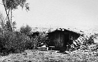 0184167 © Granger - Historical Picture ArchiveCOLORADO: DUGOUT HOME.   A frontiersman seated outside his dugout cabin in Grand County, Colorado. Photographed by William Henry Jackson, c1890.
