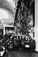0117599 © Granger - Historical Picture ArchiveELLIS ISLAND: CHRISTMAS, 1920.   Group of immigrant children photographed in front of a Christmas tree inside the registry room at Ellis Island, New York City, 1920.