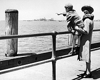 0125070 © Granger - Historical Picture ArchiveENEMY ALIEN, 1941.   A little boy points to Ellis Island, where his father is detained, having been arrested in a round-up of deportable foreigners on Long Island, New York. Photograph, 18 May 1941.