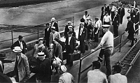 0125079 © Granger - Historical Picture ArchiveDEPORTATION, 1937.   Fifty-four unwanted foreigners leaving Ellis Island, the immigration station in New York Harbor, to board a ship taking them back to Europe, August 1937.