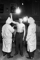0185818 © Granger - Historical Picture ArchiveIMMIGRATION: EXAM, 1921.   Members of the New York City Health Department examining an immigrant, probably at Ellis Island. Photograph, 1921.