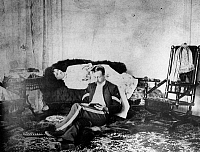 0174307 © Granger - Historical Picture ArchiveFORT STANTON, NEW MEXICO.   A U.S. military sergeant reading while a woman reclines on a sofa behind him. Photographed by Sgt. Charles Harvey, c1888.