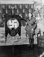 0622138 © Granger - Historical Picture ArchiveRUSSIAN NATIONAL REVOLUTIONARY PARTY.   A member of the Russian National Revolutionary Party saluting next to a swastika banner at the home of the party's leader, Anastasy Vonsyatsky, in Putnam, Connecticut. Photograph, 1937.