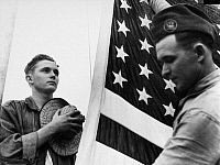 0170375 © Granger - Historical Picture ArchiveNEW DEAL: C.C.C., c1940.   A member of the Civilian Conservation Corps saluting the flag. Photograph, c1940.