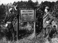 0171188 © Granger - Historical Picture ArchiveNEW DEAL: C.C.C., 1940.   Two members of the Civilian Conservation Corps standing beside a sign in Holly Springs National Forest in northern Mississippi, 11 April 1940, marking some of the area that had been replanted by the C.C.C. over the previous five years.