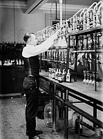 0108237 © Granger - Historical Picture ArchiveWHISKEY TESTING, 1920.   A chemist of the Internal Revenue Service, testing a half pint bottle of a bootlegger's ware for coloring additives by adding fusel oil. Photograph, 14 January 1920.