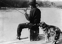 0108278 © Granger - Historical Picture ArchivePROHIBITION, 1922.   A dog trained to detect liquor sniffs at a flask in the back pocket of a man fishing on a pier on the Potomac River, during Prohibition, 1920s.