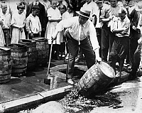 0175837 © Granger - Historical Picture ArchivePROHIBITION, c1925.   An American official dumping kegs of bootleg liquor into the sewer during Prohibition. Photograph, c1925.