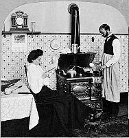 0167011 © Granger - Historical Picture ArchiveDOMESTIC COUPLE, c1903.   'Mrs. and Mrs. Henpeck get supper.' In a reversal of traditional roles, a man cooks supper while his wife reads a book. Stereograph, c1903.