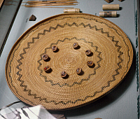 0175114 © Granger - Historical Picture ArchiveYOKUT GAMBLING TRAY.   Coiled gambling tray of the Yokut Native Americans of California, 1890-1900, with nut shells, used as dice, arranged in a circle at the center. Diameter: 53 cm.