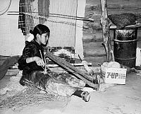 0259103 © Granger - Historical Picture ArchiveARIZONA: NAVAJO WEAVER.   12-year-old Roslyn Yazzie, a Navajo weaver, winding wool yarn in a hogan at Canyon de Chelly National Monument in Arizona. Photograph by Fred Mang, Jr., c1965