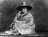 0183926 © Granger - Historical Picture ArchiveKWAKIUTL WOMAN, 1914.   The daughter of a Nakoaktok chief on the coast of British Columbia, Canada, seated on a blanket-covered board and wearing a cedar bark cape, a hat made of woven shreds of spruce roots, and a nose ring made of abalone shell. Photographed by Edward S. Curtis, 1914.