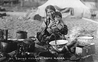 0162801 © Granger - Historical Picture ArchiveINUIT KITCHEN, 1916.   An Inuit woman and her son at an outdoor kitchen near Nome, Alaska. Photograph, 1916.