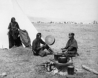 0172697 © Granger - Historical Picture ArchiveFLATHEAD COUPLE, c1905.   Mose Vandenburg, a Flathead Native American, playing a drum while seated outside a tipi next to his wife on the Flathead Reservaton in western Montana. Photographed by Edward H. Boos, c1905.