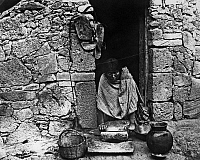 0173431 © Granger - Historical Picture ArchiveHOPI GRINDING GRAIN, 1895.   A Hopi woman grinding grain on a metate in the doorway of a stone house at Walpi, Arizona. Photographed in 1895.