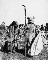 0172871 © Granger - Historical Picture ArchiveASSINIBOIN DANCERS, 1906.   Two Assiniboin boys wearing the costumes of a leader (right) and a warrior of the Fool's Dance Society, on the Fort Belknap Reservation in Montana. They both have whistles in their mouths, and the boy at right holds a deer hoof rattle. Photographed by Sumner W. Matteson, July 1906.