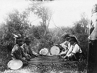 0173404 © Granger - Historical Picture ArchiveOJIBWA GAME, c1910.   Four Ojibwa Native American men playing a moccasin game, in which participants guess the location of a marked bullet, on the White Earth Reservation in northern Minnesota. Photographed by Frances Densmore, c1910.